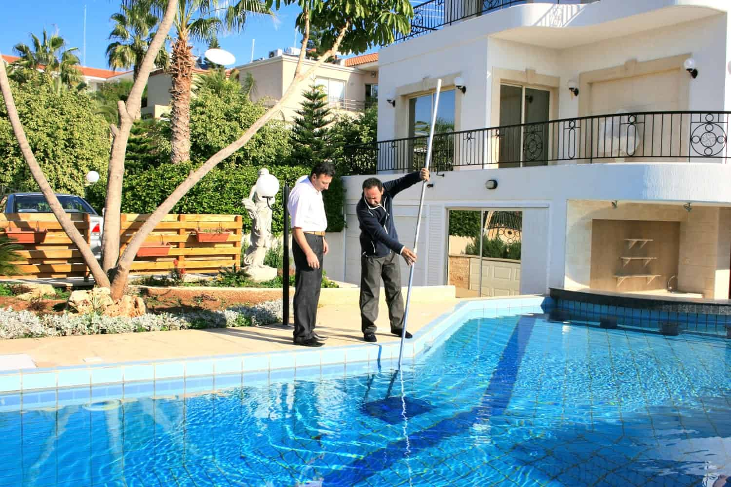 Two men at the side of the pool looking at the water as one of them cleans it with a pool cleaner.