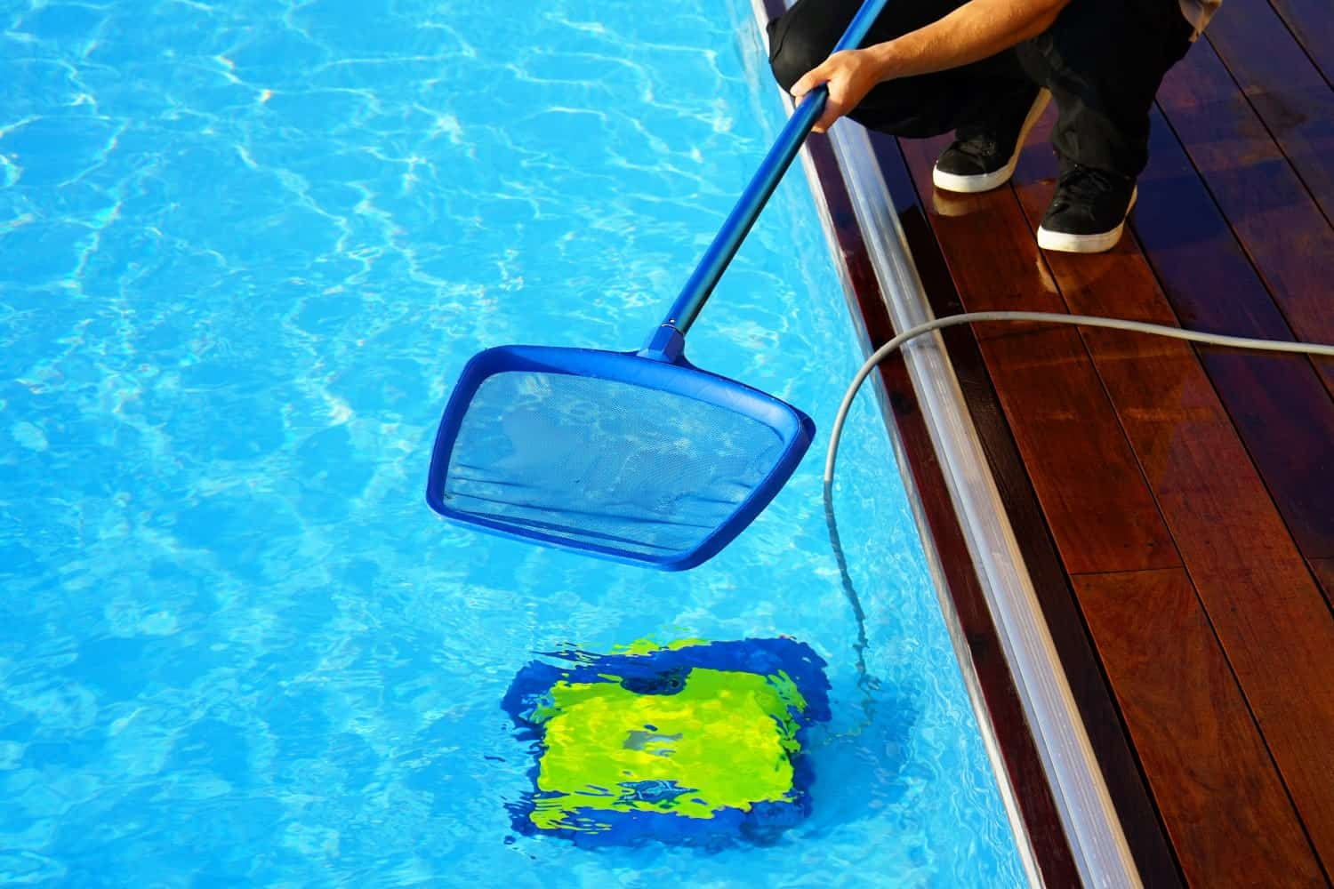 Using a net to remove some debris from the pool while a pool cleaner is underwater.