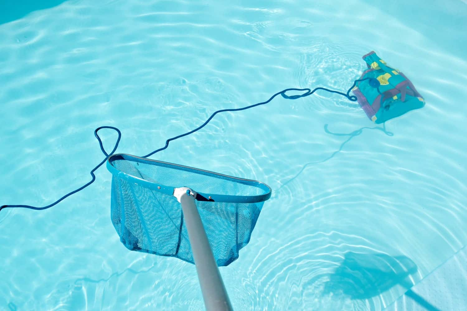 A net above water and a pressure pool cleaner at the bottom of a pool.
