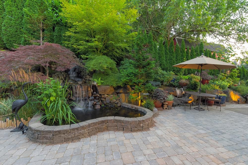 Backyard garden hardscape with a pond.