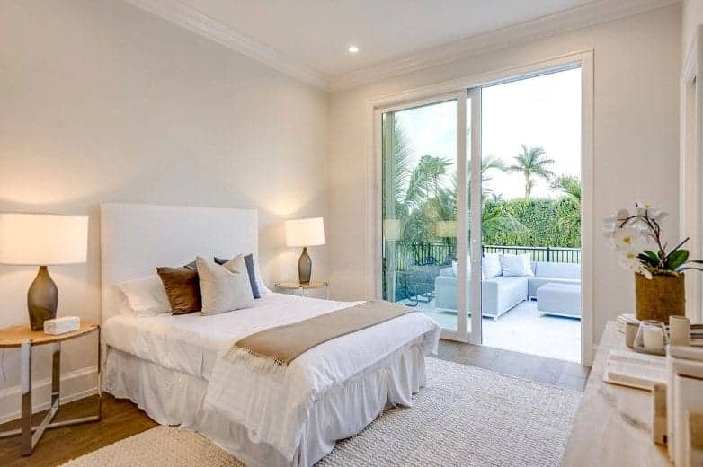 The simplicity of this Beach-style bedroom is elevated by the large glass sliding doors that bring in an abundance of natural light to the white bed that is flanked by large table lamps on bedside tables that stand out against the dark hardwood flooring.