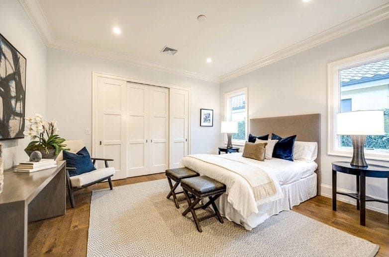 The dark wooden furniture of this Beach-style bedroom matches well with the white bed that has a beige cushioned headboard that stands out against the light gray walls adorned with mounted artworks and decors.