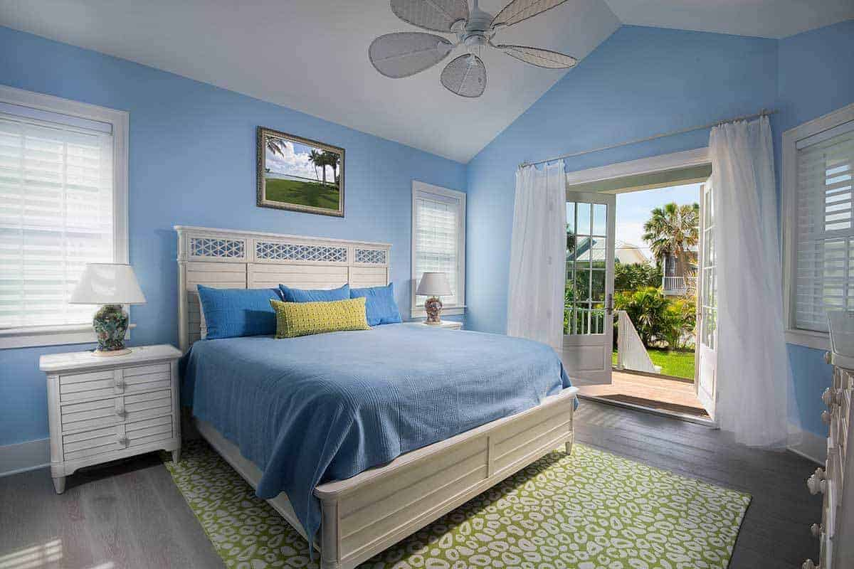 This colorful Beach-style bedroom has blue walls matching the blue sheets and pillows of the white traditional bed matching the white wooden bedside drawers and the white cathedral ceiling bearing a ceiling fan over the green patterned area rug.