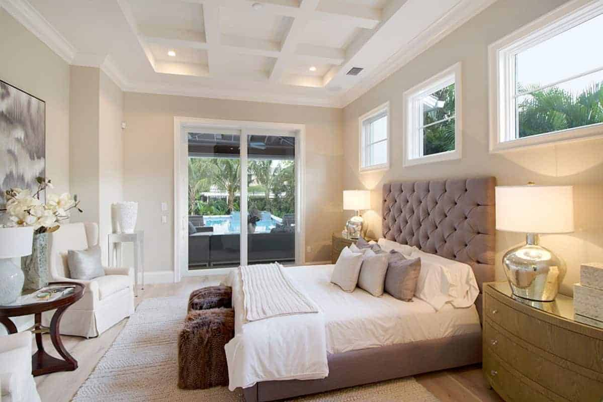 The high ceiling of this primary bedroom has a white coffered finish to it that goes well with the beige walls complemented by the warm yellow lights of the table lamps flanking the gray bed over a white woven area rug.