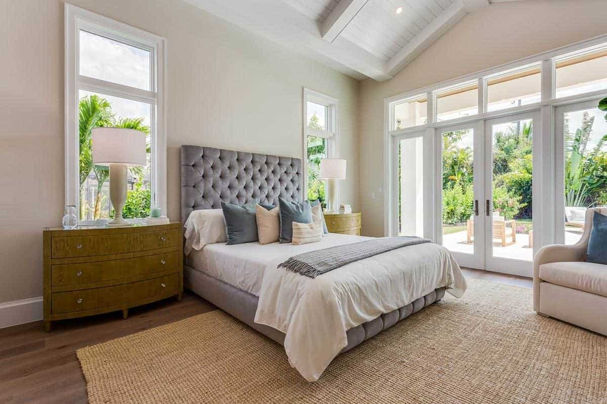 The rustic brown woven area rug over the hardwood flooring is a nice complement to the gray bed that is flanked with bedside drawers. The brightness of this bedroom is due to the high cathedral ceiling and the glass doors.