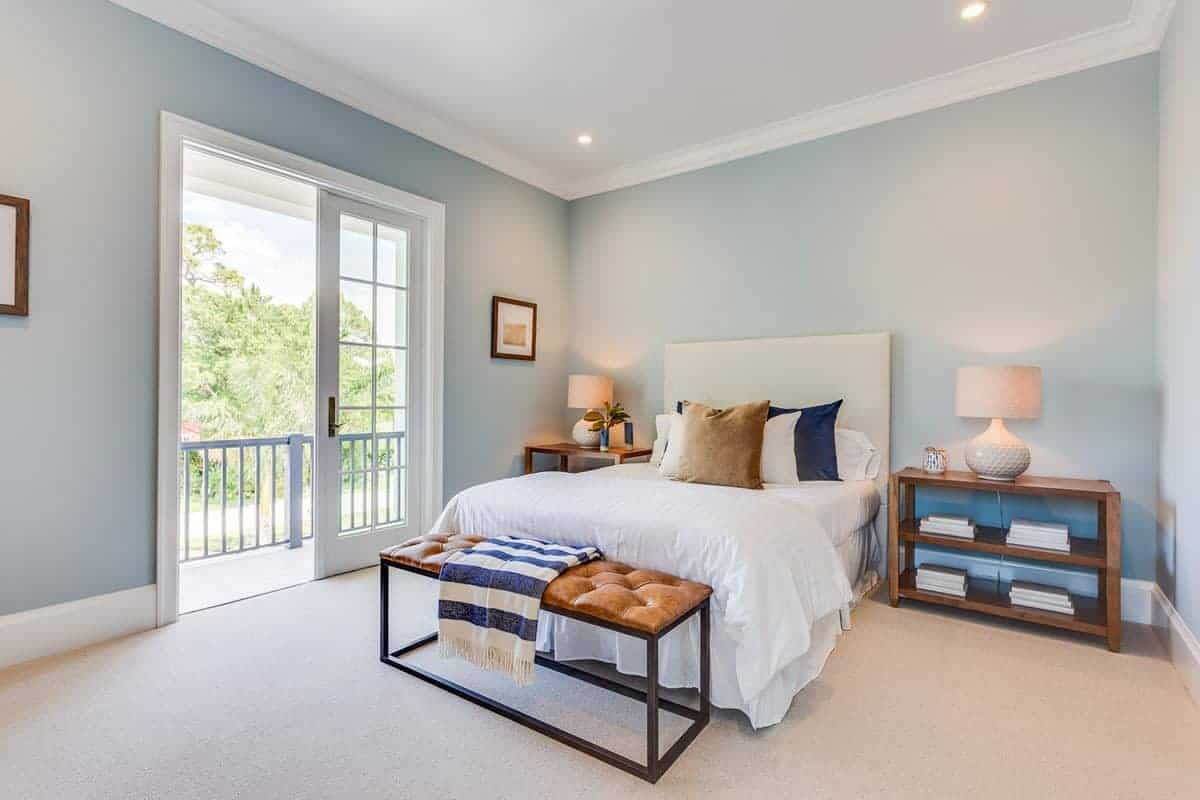 The bright and cheerful demeanor of this Beach-style bedroom is due to the light blue walls augmented by a white ceiling with recessed lights and white molding that pairs well with the frames of the white glass doors.