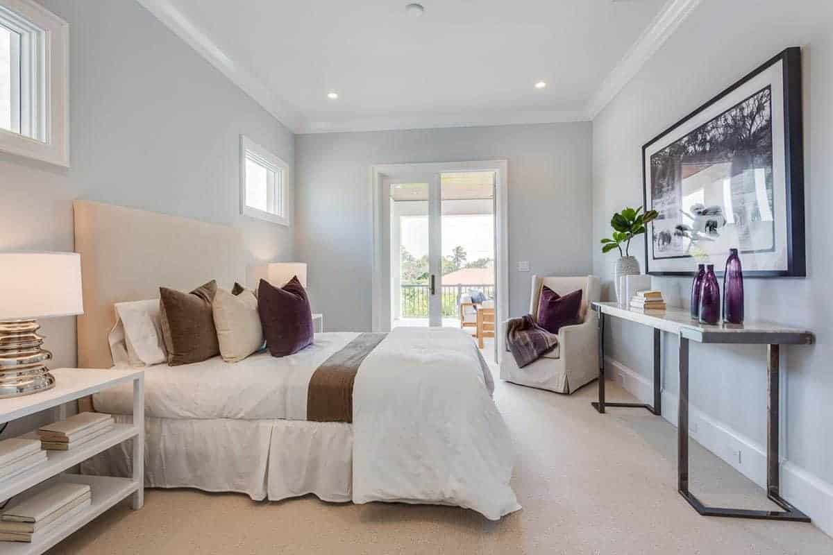 The beige cushioned headboard of the traditional bed pairs well with the beige carpeted flooring. This is complemented by the white elements of the bed sheets, bedside tables and the white ceiling.