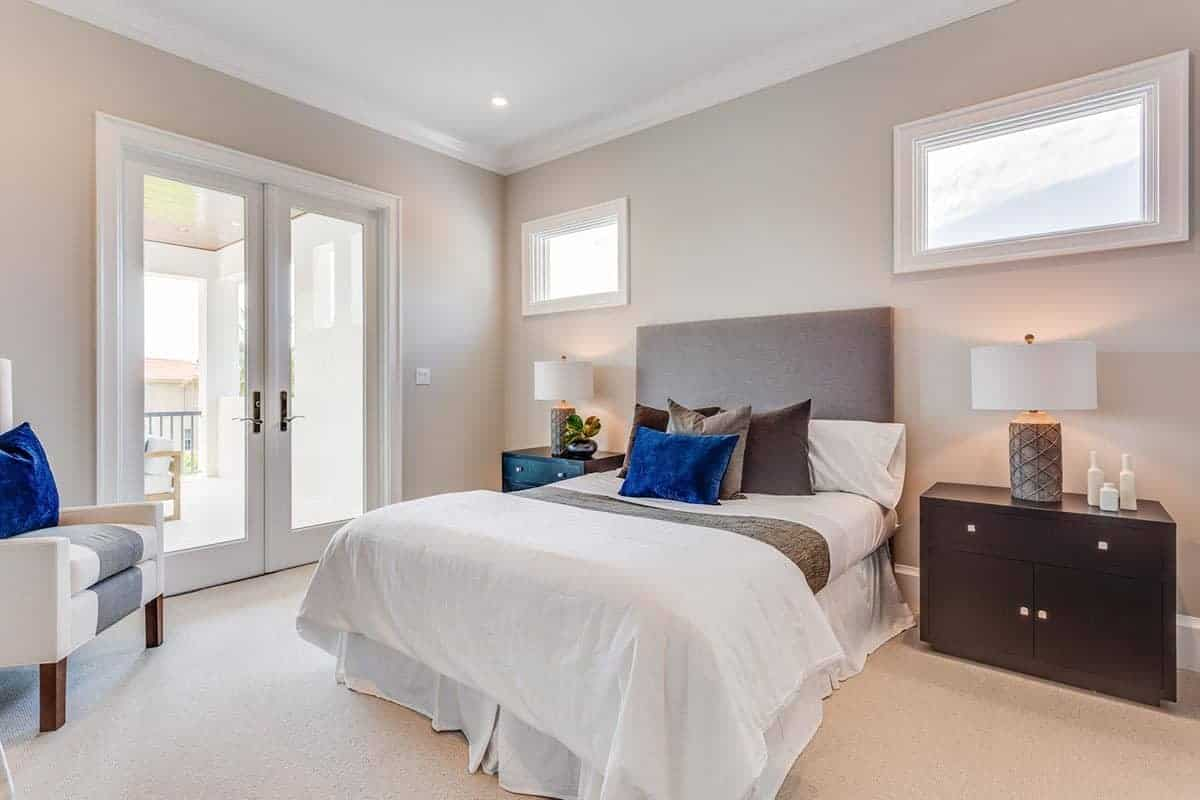The warmth and comfort that exudes from this bedroom is mostly due to the yellow lights of the table lamps on the dark wooden bedside drawers flanking the white bed. This bed has a beige headboard that matches well with the beige carpeted flooring and the walls.