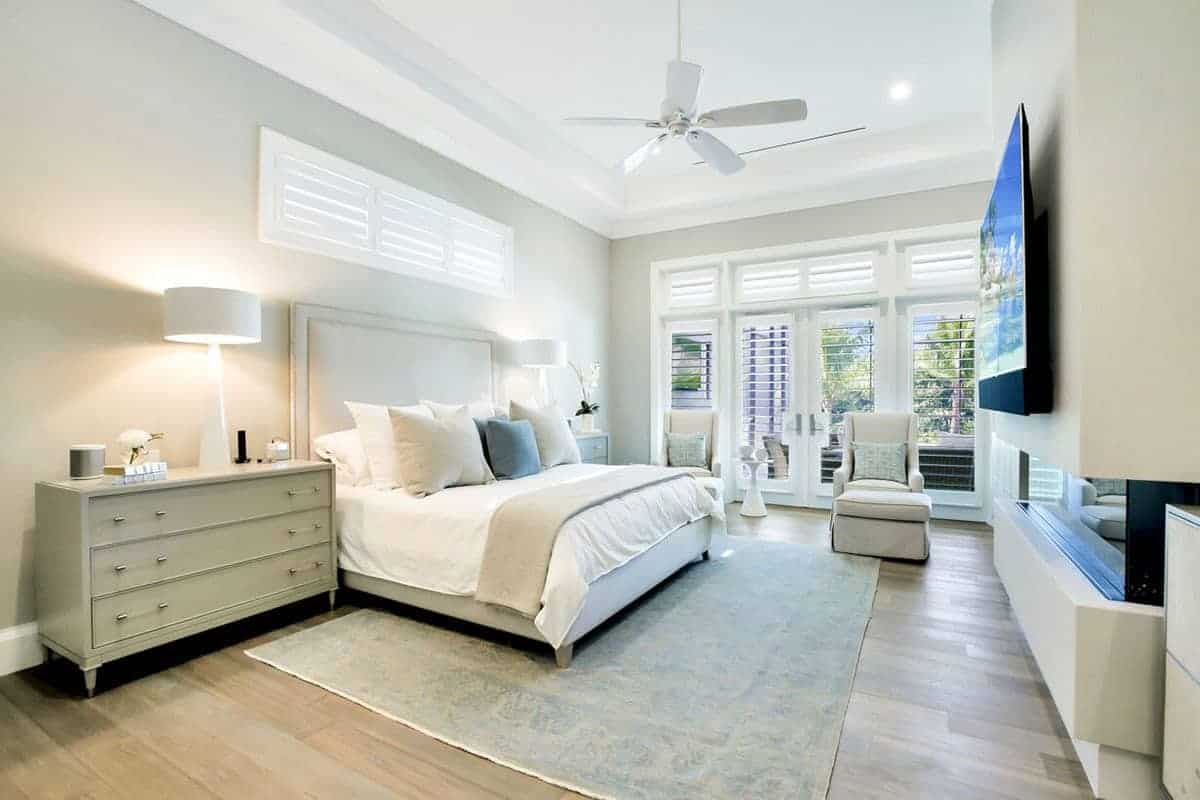 Underneath the traditional beige bed that has a beige cushioned headboard is the cheerful light green patterned area rug that reflects the hue of the walls complimented by avocado green bedside drawers bearing table lamps on them.