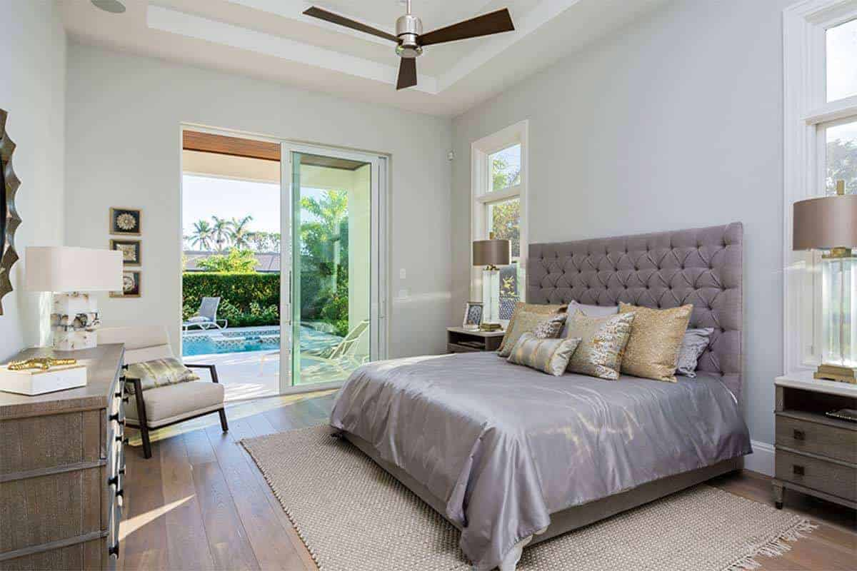 The modern ceiling fan with a light attached to it stands out against the white tray ceiling. This matches with the frames of the white glass windows and the glass doors that feature a lovely poolside scenery for the traditional bed with gray headboard.