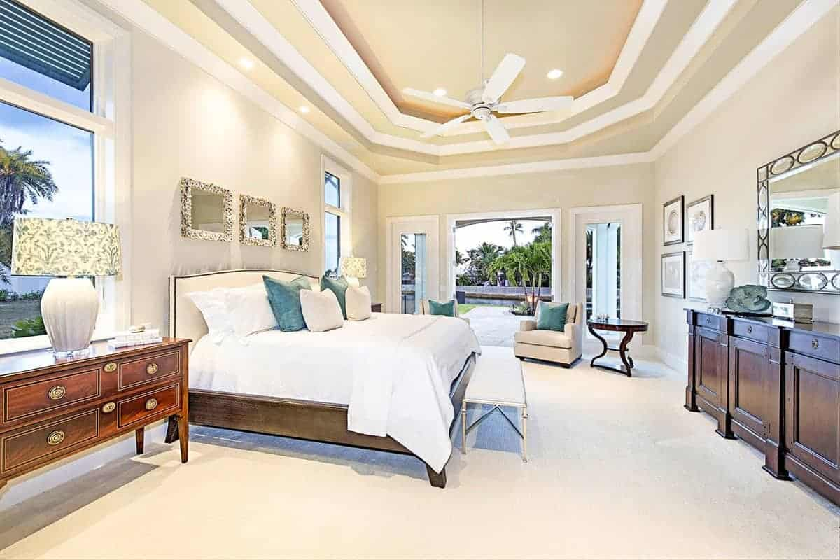 The beige tray ceiling of this Beach-style bedroom has white trimmings that emphasizes the peculiar octagonal shape of the middle trays with a white ceiling fan hanging over the traditional bed paired with a small bench at its foot.
