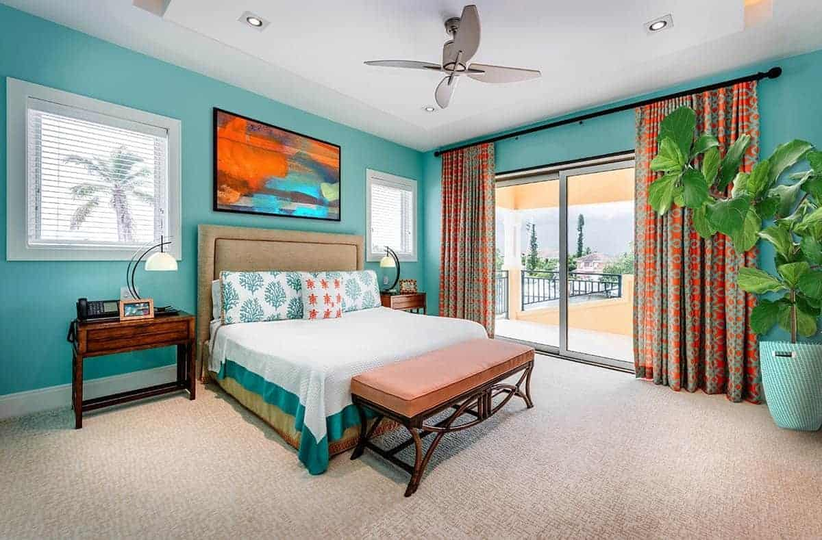 This primary bedroom is dominated by the green hues that can be seen on the walls, bed sheet trimmings, patterned pillows and pot of the potted plant in the corner. This is contrasted by the red patterned curtains flanking the glass doors.