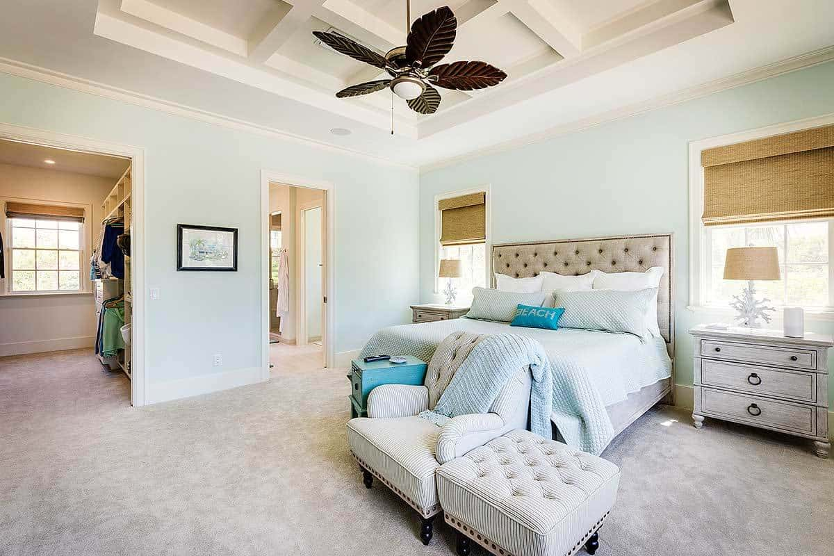 The white coffered ceiling makes the dark ceiling fan stand out with its unique leaf designs that accentuate the simplicity of the light blue walls and gray tufted headboard flanked by gray wooden bedside drawers that blend with the gray carpeted flooring.