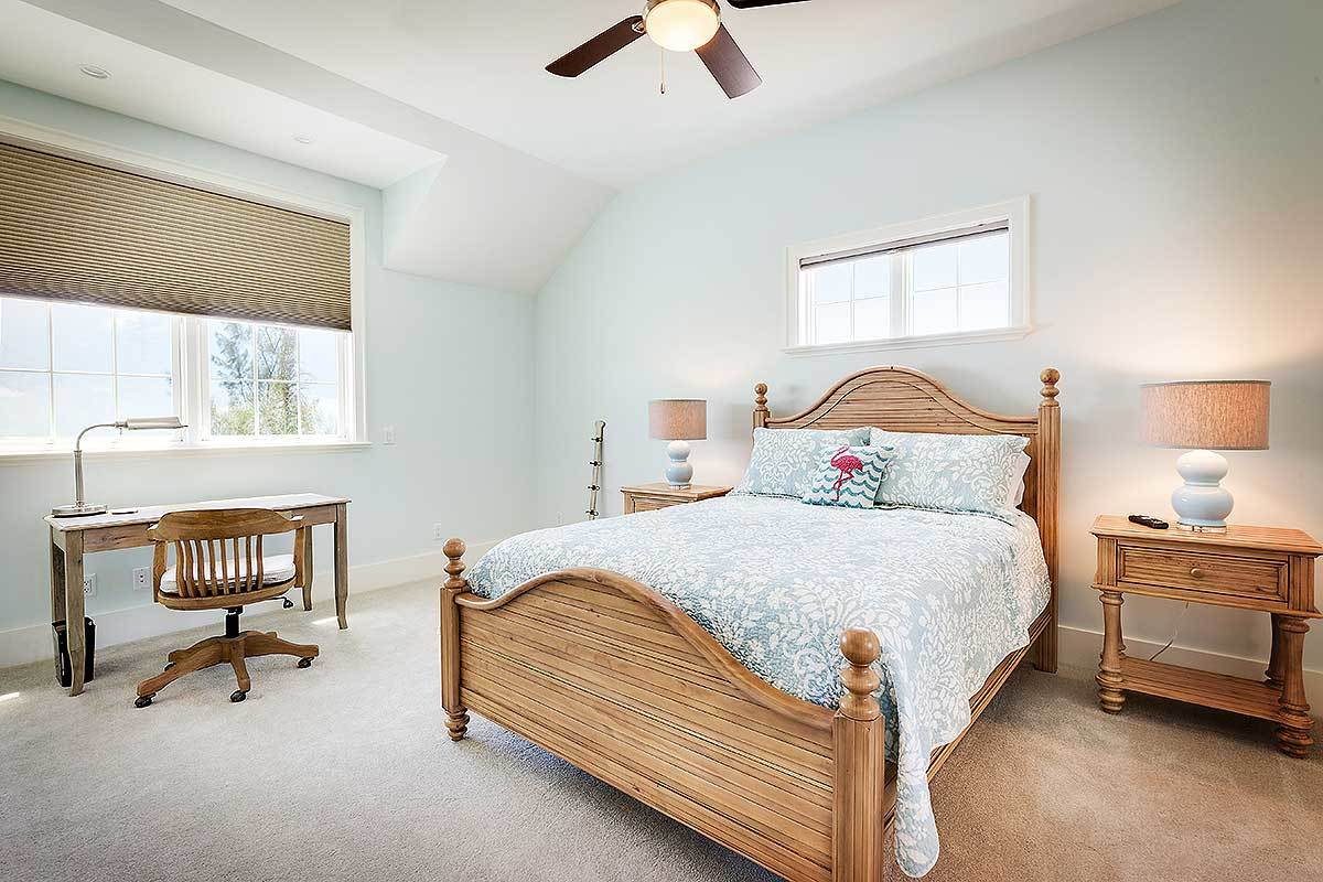 The wooden elements of the sleigh bed, bedside drawers and the swivel chair at the study area are a nice accent to the light blue hue of the walls augmented by the white arched ceiling with a brown ceiling fan in the middle.