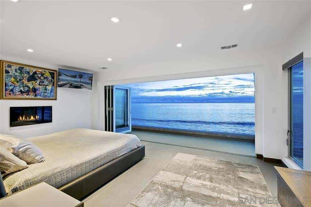 The highlight of this Beach-style bedroom is the amazing view of the ocean right outside the folding glass doors that take up most of the wide wall on the foot of the gray platform bed that complements the light gray flooring.