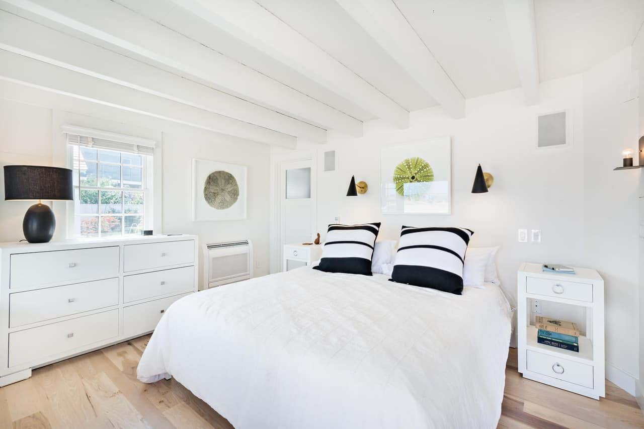 The small bedroom is mostly dominated by the white elements of the white ceiling with exposed wooden beams matching the white bed and the white bedside tables and wooden dresser that blends with the white walls. This is complemented by the hardwood flooring and the accents of the black lamps and the black and white pillows.
