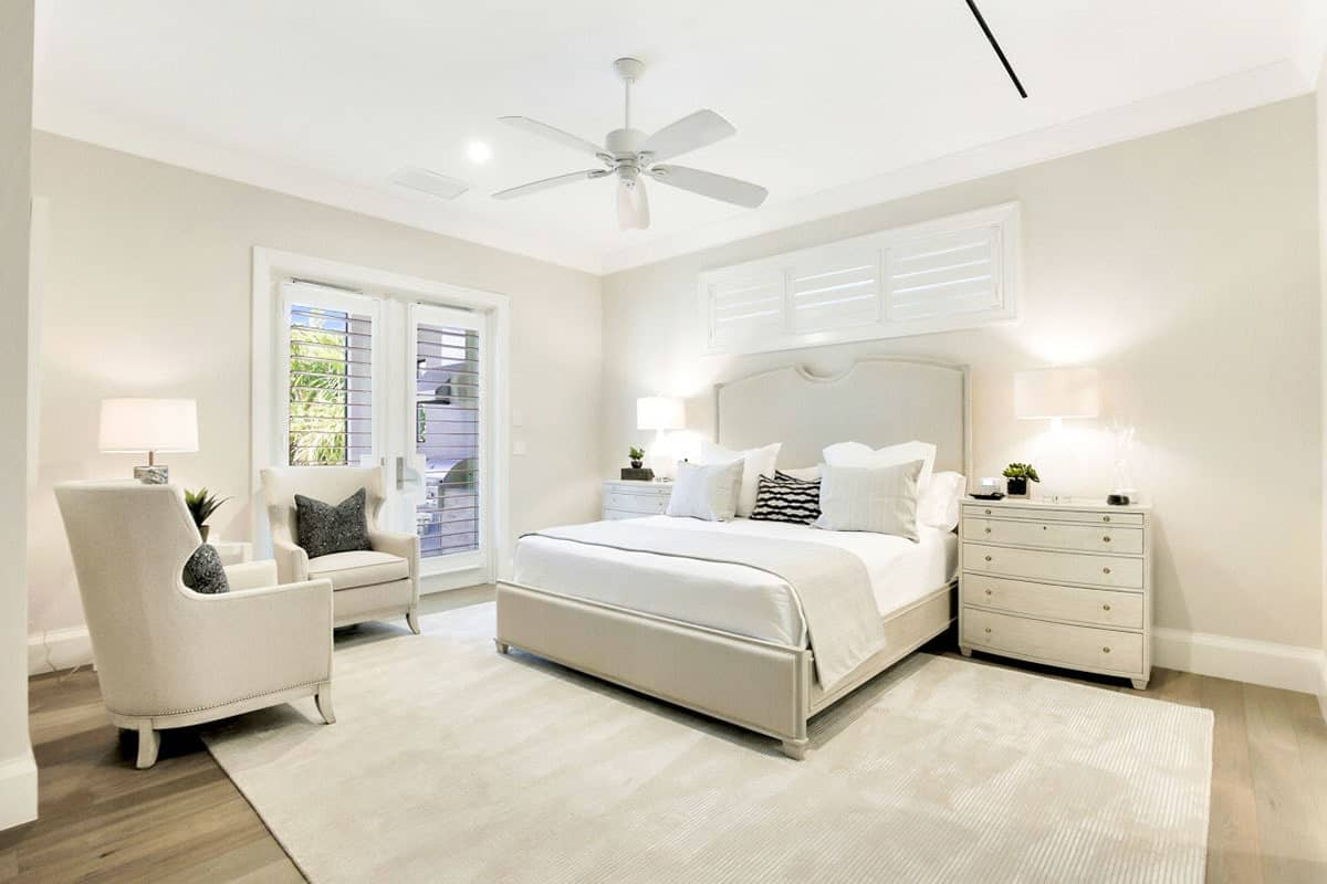 The pairing of the white ceiling and the beige walls are reflected by the beige traditional bed with a large cushioned headboard flanked by bedside drawers that complements the white sheets and pillows of the bed.