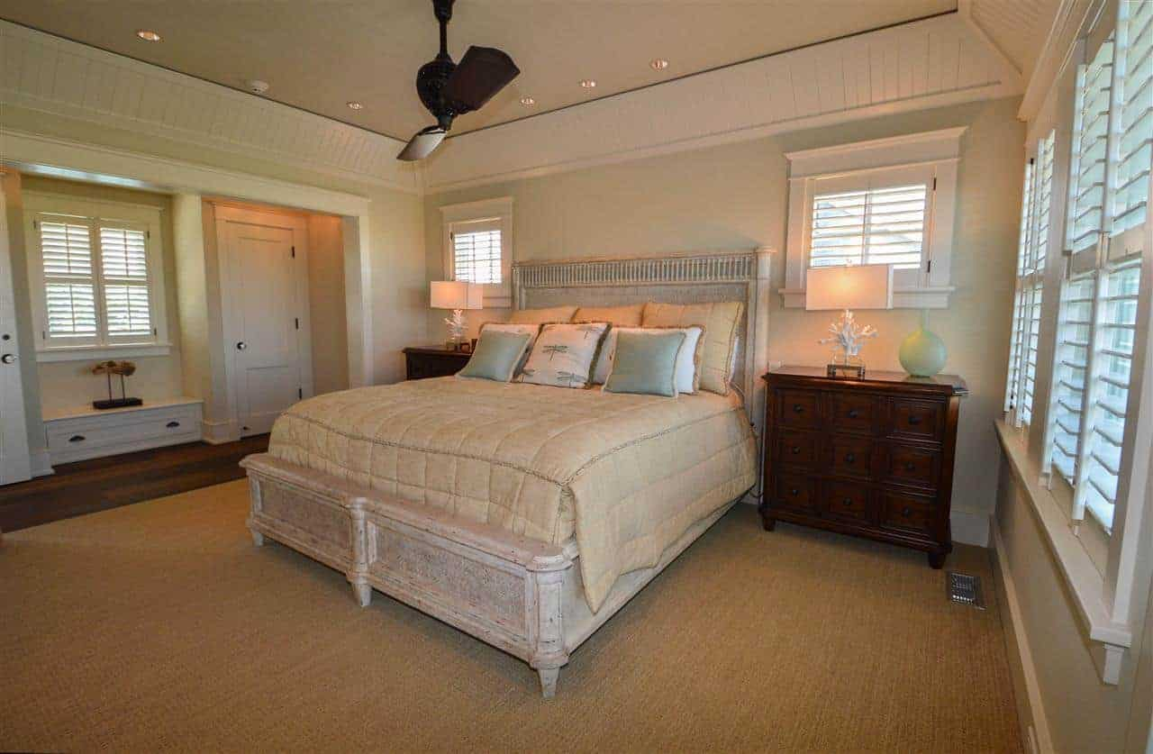 The dark brown carpeted flooring of this bedroom is a complement to the dark wooden bedside drawers that stands out against the light green walls that go well with the light gray distressed wooden traditional bed.
