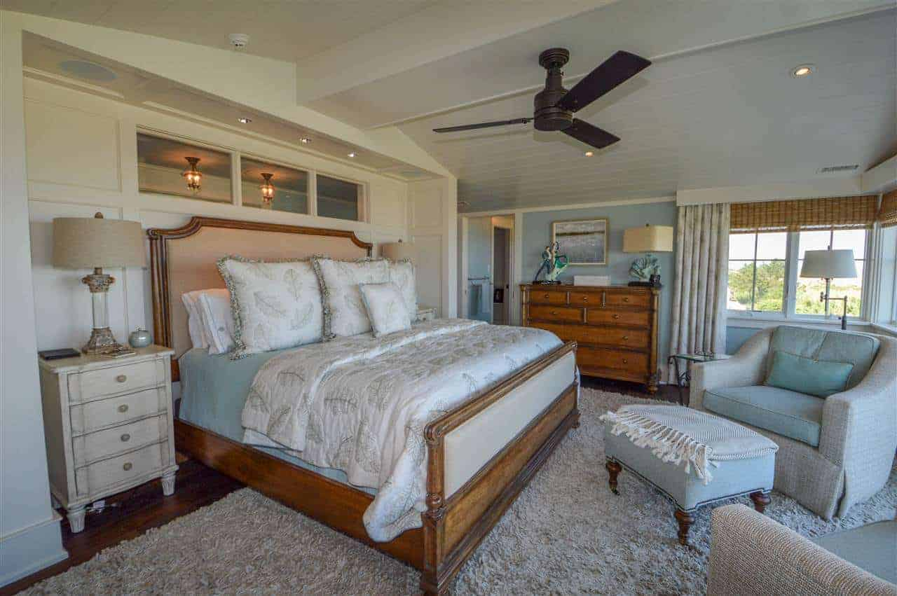 The wooden sleigh bed and the dresser on the side stands out against the light hues of the green walls and white cathedral ceiling that is complemented by the light gray furry area rug covering most of the hardwood flooring.