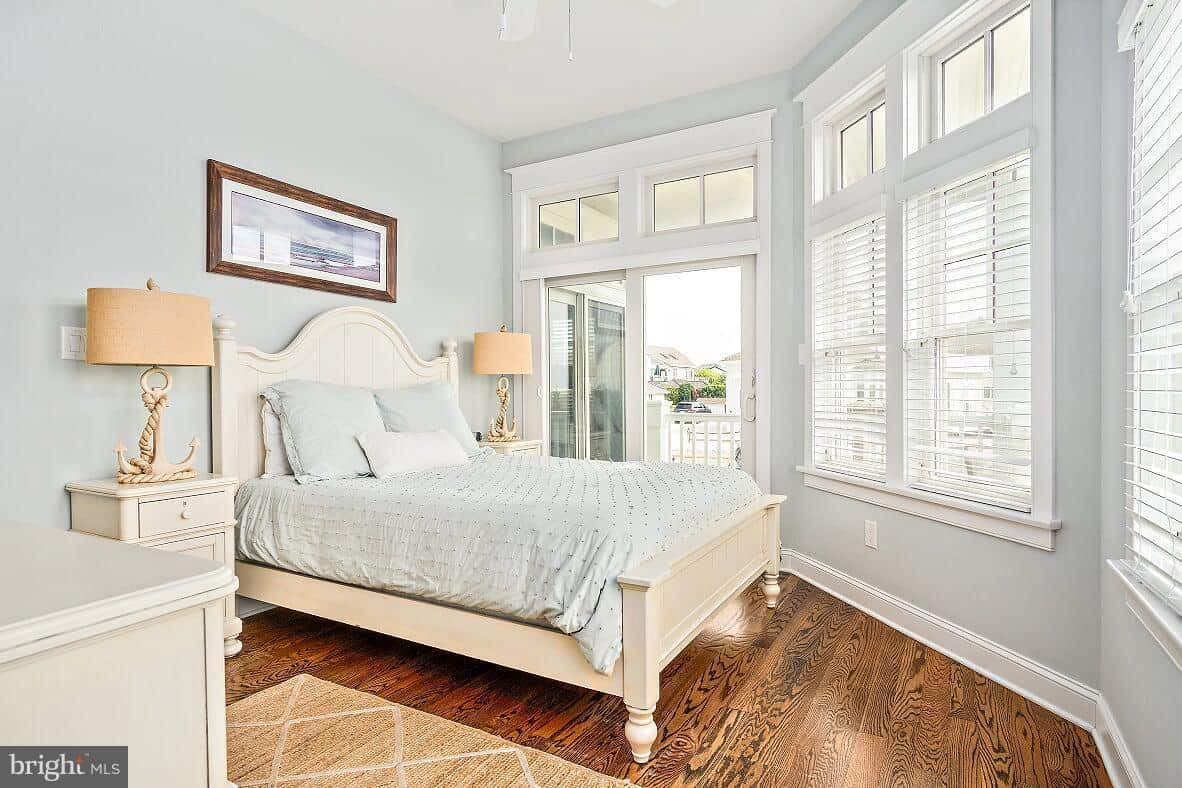 The small and irregular-shaped bedroom has dark hardwood flooring that contrasts the light gray walls illuminated by the natural lights coming in from the white windows. This goes well with the beige traditional bed that is flanked with beige table lamps with anchor design.