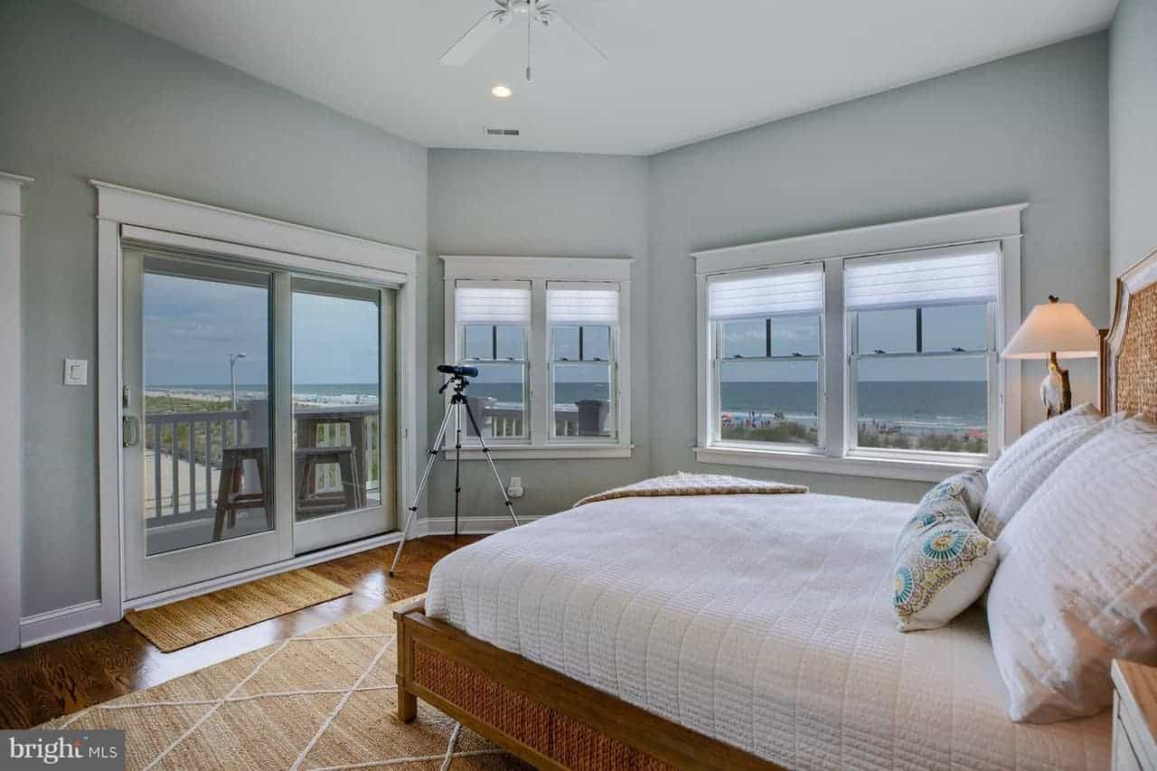 This charming bedroom emphasizes the amazing seaside scenery outside of the row of windows and sliding glass doors that dominate the light gray walls contrasting the hardwood flooring and the bed frame.