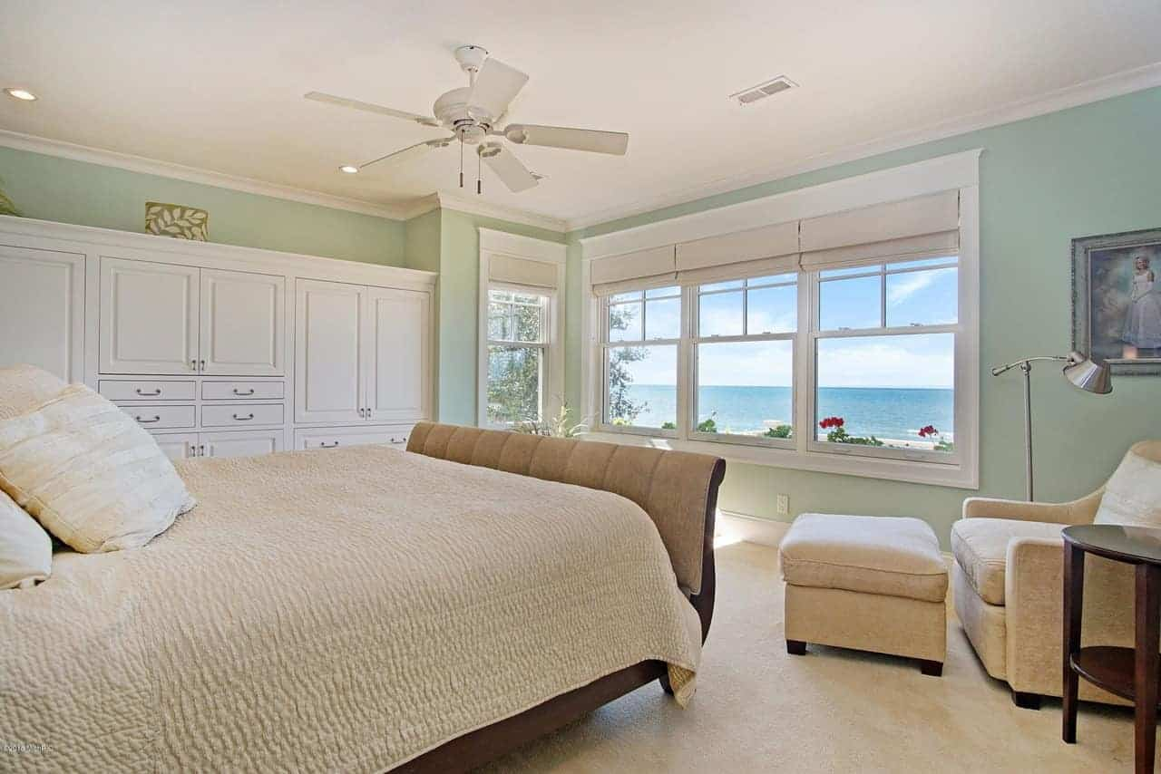 The light green walls of this Beach-style bedroom go well with the amazing view of the ocean that is seen through the white windows that bring in an abundance of natural lighting to the beige carpeted flooring and bed sheet of the wooden sleigh bed.