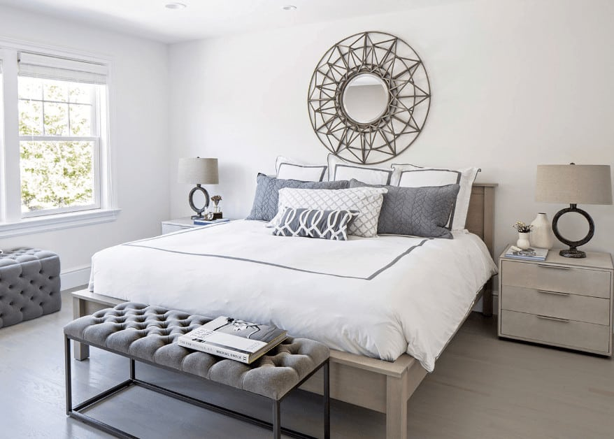 Above the gray wooden traditional bed is a charming circular mirror with sun-like designs to it mounted on the white wall that is complemented by the gray bedside drawers bearing modern table lamps with gray hoods matching the gray hardwood flooring.