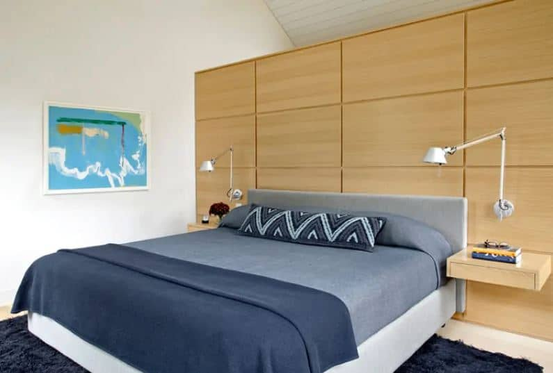 The gray headboard of the traditional bed is against a wooden wall panel with an elegant finish and a light hue that supports the wall-mounted lamps over hanging shelves on each side of the bed. This is contrasted by the navy blue sheets and the area rug underneath.