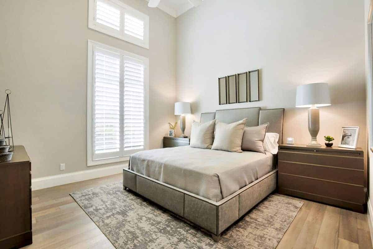 The highlight of this room is the brilliant high ceiling that is complemented by the light gray walls adorned with a white framed window as well as a couple of wooden bedside drawers on either side of the gray cushioned headboard accented with artworks above it.
