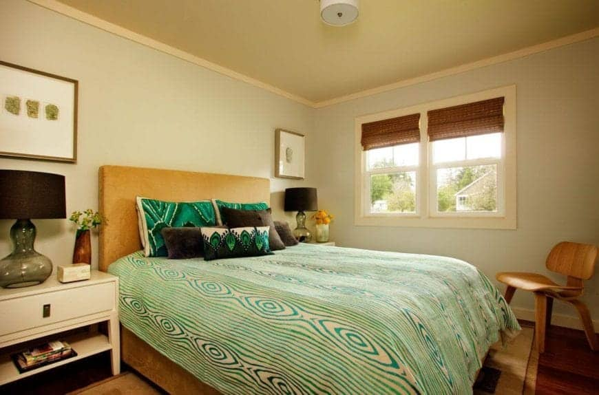 The green patterned bed sheet stands out against the brown headboard of the traditional bed that is flanked with white bedside drawers that complement the light green walls along with the white frames of the window.
