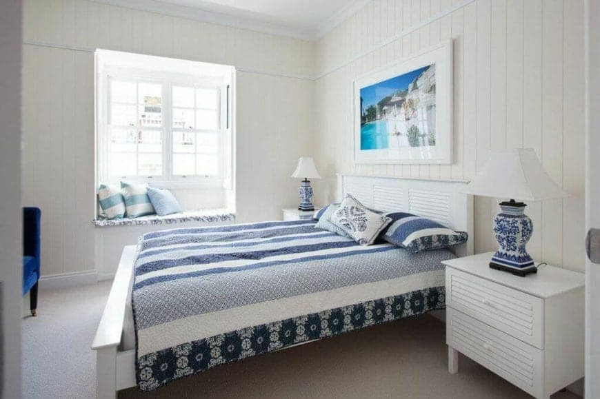 The blue patterned table lamps that stand out against the white bedside drawers are a perfect match for the blue patterned bed sheets and pillows of the white wooden sleigh bed that complement the shiplap walls adorned with a photograph of the beach mounted above the bed.