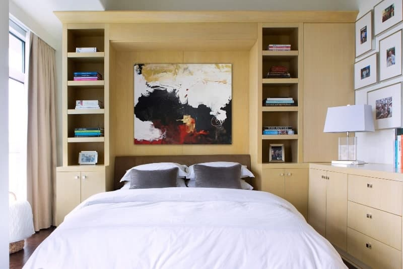 The dark brown headboard of the traditional bed is against a large wooden structure that houses shelves and cabinets extending to the dresser on the adjacent wall with a modern table lamp on it that matches the white sheets.