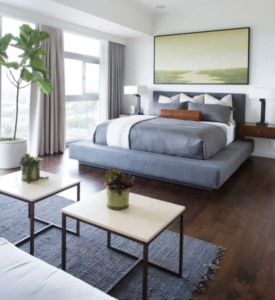 The dark gray platform bed goes well with the dark hardwood flooring for a unique aesthetic that complements the white walls adorned with a large painting mounted above the bed illuminated by the large windows.