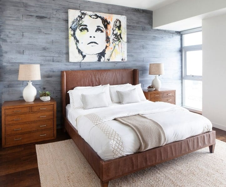 The beautiful framed artwork is a lovely complement to the gray wall behind the brown headboard of the bed that matches with the hardwood flooring and the two bedside drawers that contrast the bright white walls and ceiling.