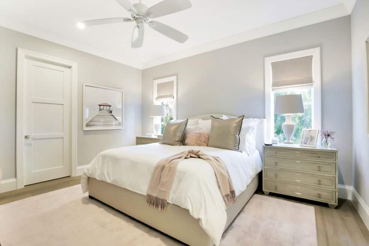 The elegant gray bedside drawers of this bright Beach-style bedroom matches the gray cushioned bed and its pillows that stand out against the white sheets. This is further softened by the combination of the hardwood flooring and the light beige area rug.