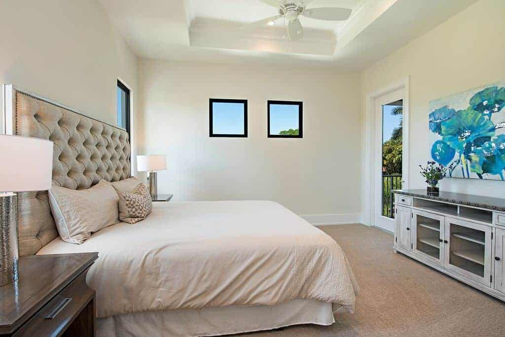 The beautiful traditional bed has a large tufted beige headboard that goes well with the beige walls and beige carpeted flooring. Across from the headboard is a colorful floral painting for a dash of color to the Beach-style bedroom.