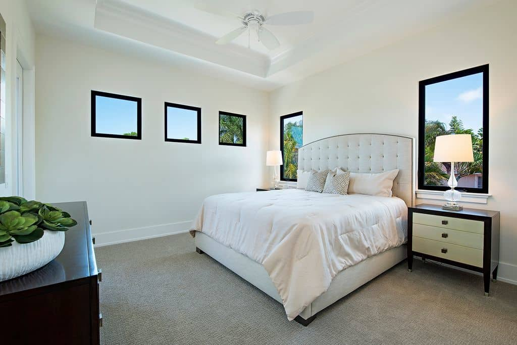 The gray carpeted flooring complements the beige walls and white tray ceiling with a white ceiling fan hanging in the middle over the white traditional bed flanked by elegant bedside drawers with lamps and a window behind.