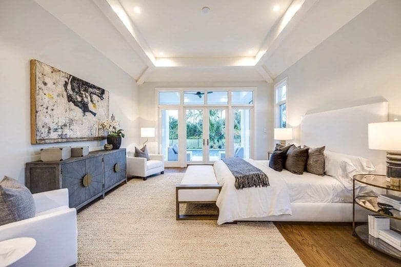 The white coffered ceiling is further brightened by the white recessed lights. This is complemented by the warmth of the lamps on both sides of the white bed that contrasts the dark hardwood flooring mostly covered by a woven area rug.