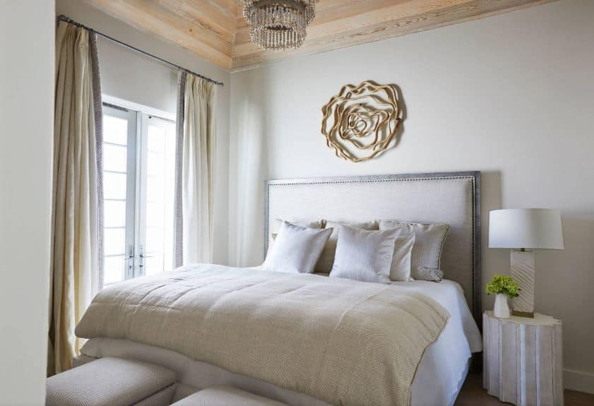 The beige cushioned headboard of the bed is adorned with a brass artwork mounted on the white wall above near the wooden ceiling that has a crystal chandelier hanging over the white and beige sheets of the bed.