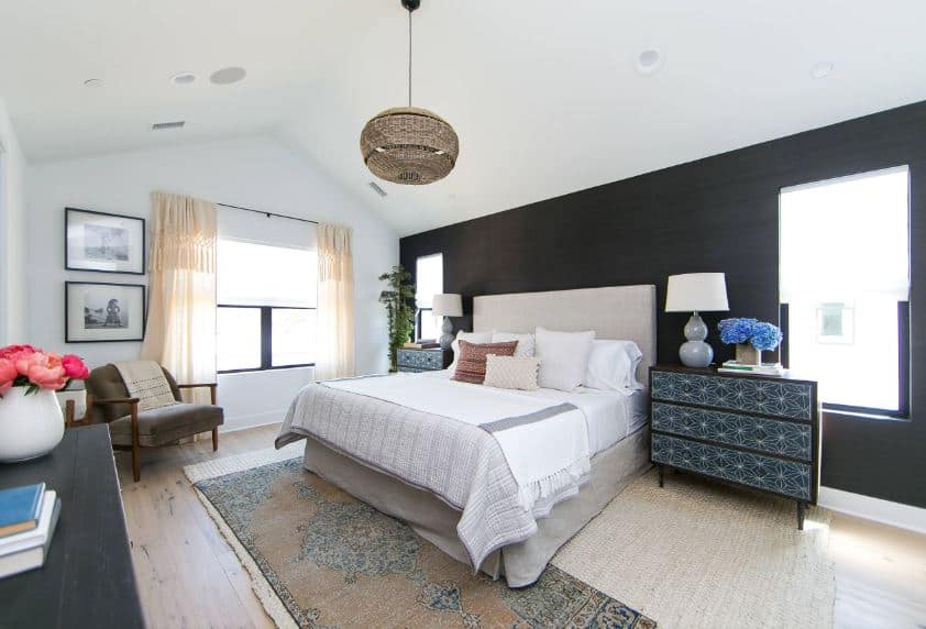 The bedside drawers flanking the beige headboard of the bed have elegant geometric patterns on its that sets a complex contrast to the black wall behind the head of the bed that contrasts the white cathedral ceiling.