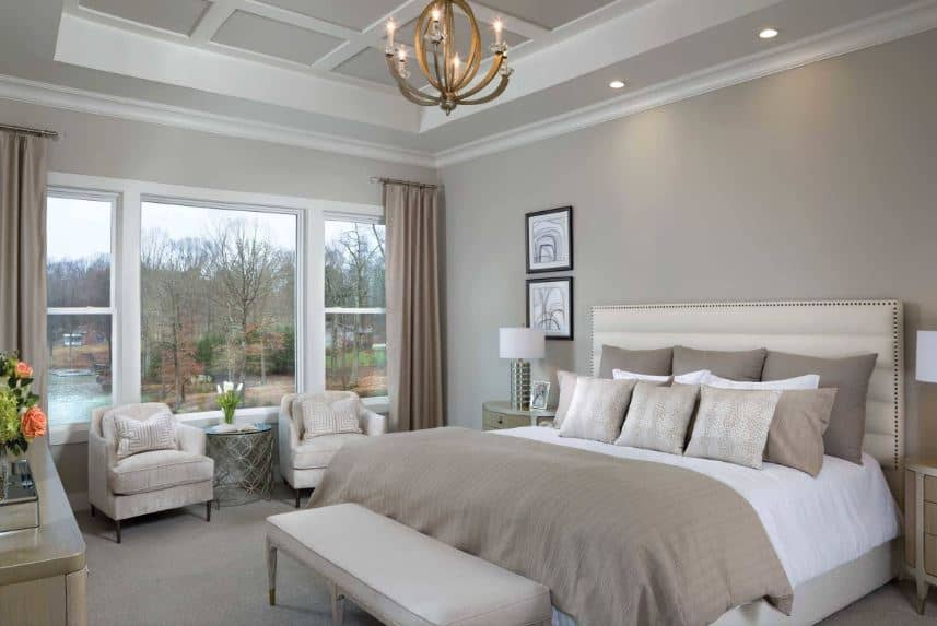 The highlight of this predominantly gray Beach-style primary bedroom is the elegant brass chandelier hanging near the tray ceiling with gray coffer patterns in the middle tray. This is a perfect match for the gray walls, gray floors and elements of the traditional bed.