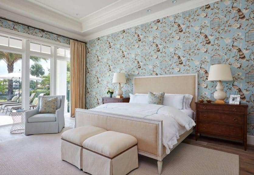 The intricate wallpaper catches the attention in this primary bedroom. It has images of flowers and birds in it that is given a light blue background for that chic aesthetic that goes well with the white tray ceiling and the beige traditional bed on the beige area rug.