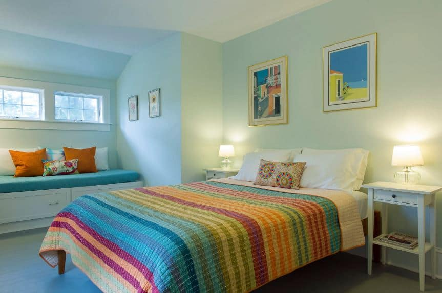 This simple bedroom has a rainbow-colored bed sheet that sets the tone of this colorful Beach-style bedroom that has a lovely sitting area on the side below the windows that go well with the light hue of the walls.
