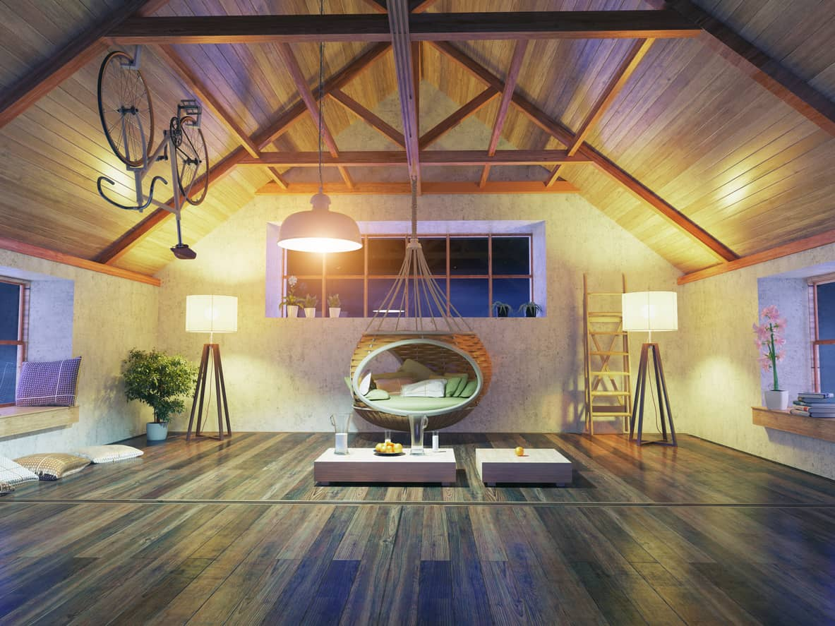 Sitting area at a warm loft boasting a rattan hammock chair that hung from cathedral ceiling with exposed wood beams. It is lighted by a pair of floor lamps and a white dome pendant.
