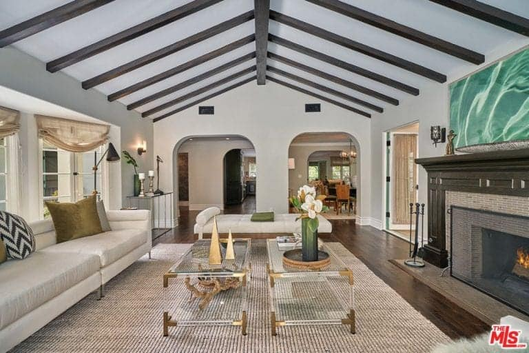 Magnificent living room boasts open arched doors and a cathedral ceiling with exposed wood beams. A pair of glass coffee tables stand in the middle of a white sofa and fireplace.