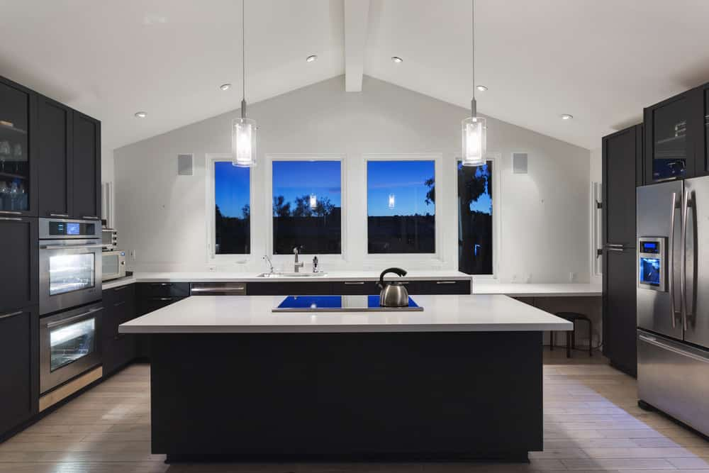 Modern kitchen with a gorgeous black and white color scheme. It has a marble top breakfast island with built-in cooktop illuminated by a pair of glass pendants and recessed lights mounted on the cathedral ceiling.