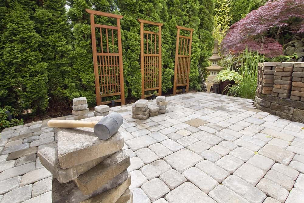 Stack of brick pavers used as materials for a garden hardscaping.