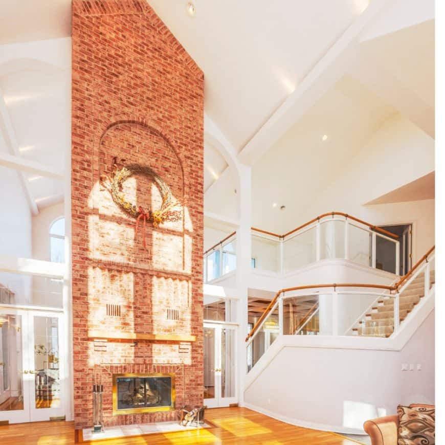 Elegant white house accented with a red brick pillar fitted with a modern fireplace that's fixed to a high cathedral ceiling.