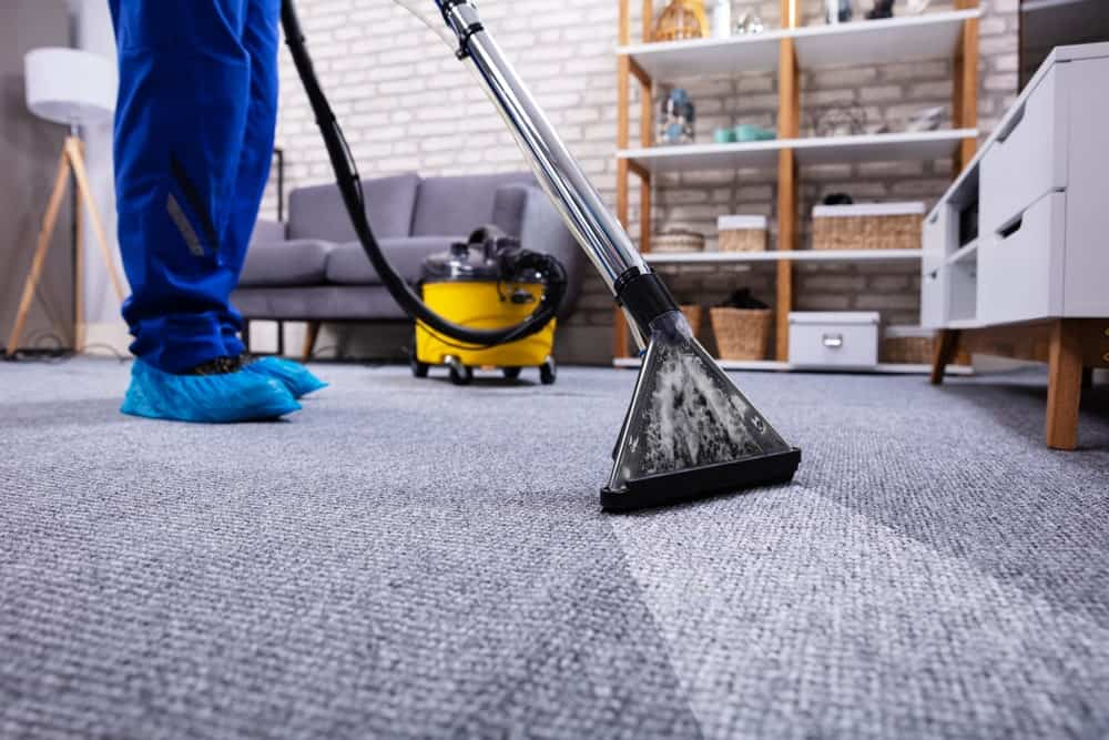 Carpet cleaning using a machine.