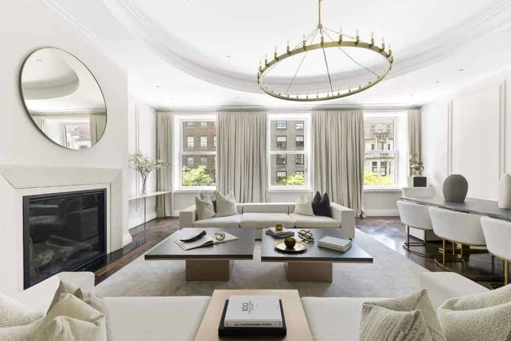 Light and airy living room with a fireplace and modern white sectionals flanking a pair of wooden coffee tables over a beige rug. The room is decorated with a round mirror and chandelier that hung from the tray ceiling.